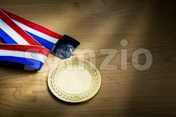 Generic sporting event gold medal with red and blue ribbon on wooden surface against ray of light.  Fine art ...