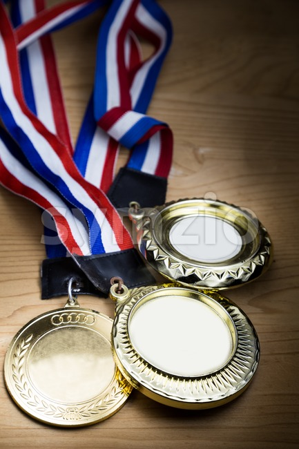 Three generic sporting event gold medal with red and blue ribbon on wooden surface against ray of lights.  Fine ...
