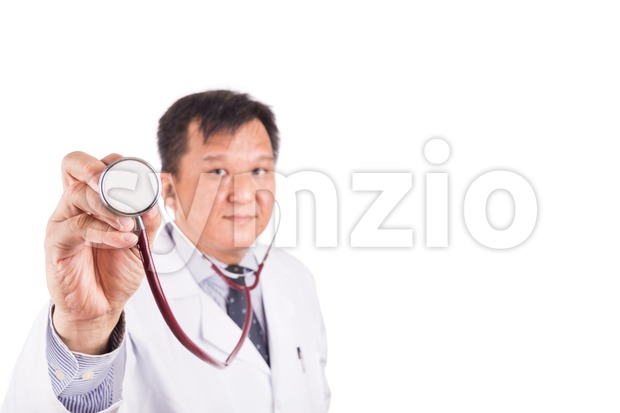 Selective focus on stethoscope held by matured and confident Asian male medical doctor in background