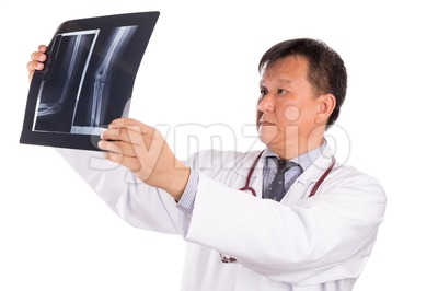 Matured Asian orthopedic medical doctor examining X-ray film Stock Photo