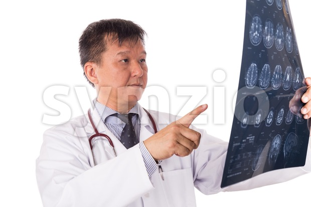 Matured Asian neurology medical doctor examining head MRI images Stock Photo