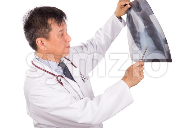 Matured Asian medical doctor examining lungs X-ray negative film Stock Photo