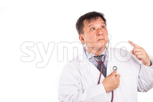 Matured and funny Asian medical doctor listening to own heartbeat using stethoscope