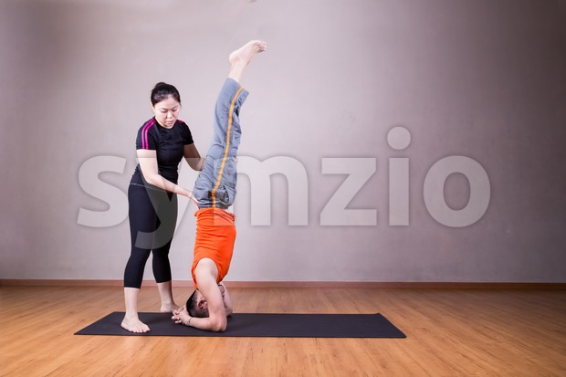 Yoga instructor guiding student perform head stand pose or Sirsasana Stock Photo
