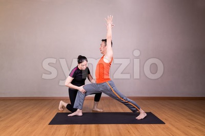 Yoga instructor correcting student performing Warrior 1 or Virabhadrasana 1 Stock Photo