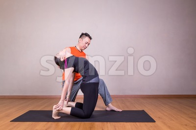 Yoga instructor guiding student perform Camel pose or Utrasana Stock Photo