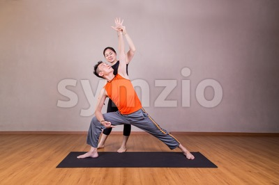 Yoga instructor guiding student perform extended side angle pose Stock Photo