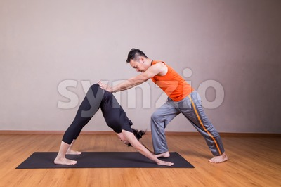 Yoga instructor guiding student perform downward facing dog pose Stock Photo
