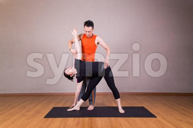 Yoga instructor guiding student perform triangle pose or Trikonasana Stock Photo