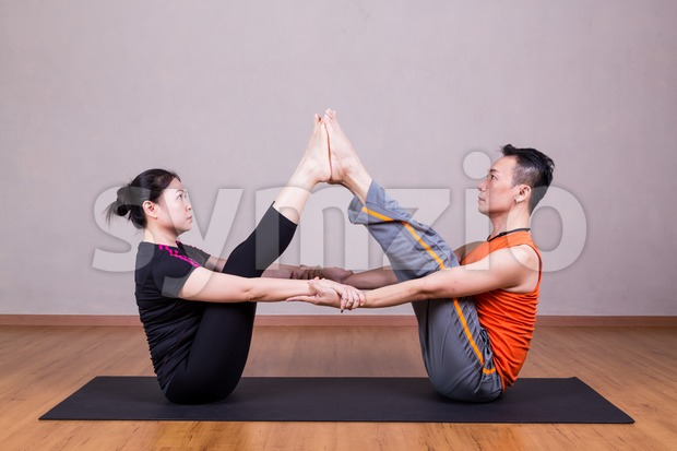 Partner Buddy Boat Yoga Pose by a couple Stock Photo