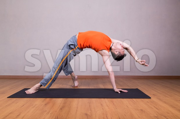 Man performs advanced yoga pose Stock Photo