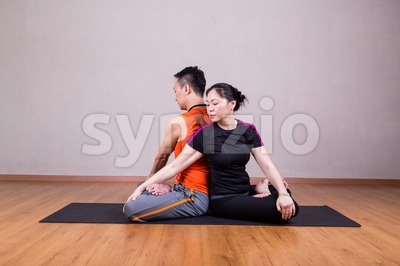 Partner Twist Yoga Pose by a couple Stock Photo