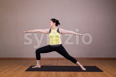Female performing the Warrior 2 or Virabhadrasana 2 yoga pose Stock Photo
