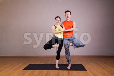 Couple perform Double Tree yoga partner pose Stock Photo