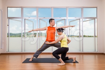 Yoga instructor correcting student performing Warrior 2 or Virabhadrasana 2 Stock Photo