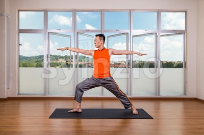 Yoga practitioner performing Warrior 2 or Virabhadrasana 2 pose Stock Photo