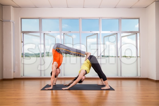 Partner yoga pose of double downward dog by a couple Stock Photo