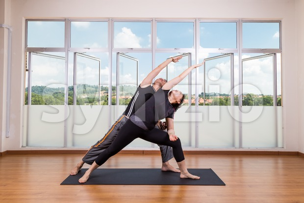 Couple perform series of Extended Side Angle yoga partner pose Stock Photo