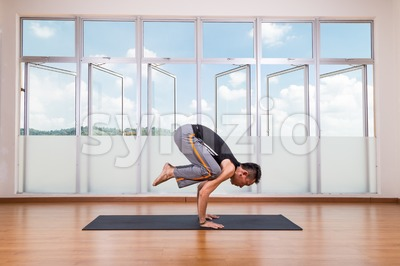 Yoga practitioner performing Crane or Crow pose or Bakasana pose Stock Photo