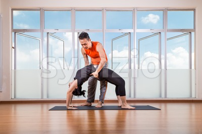 Yoga instructor assisting student perform Backbend or Chakrasana pose Stock Photo