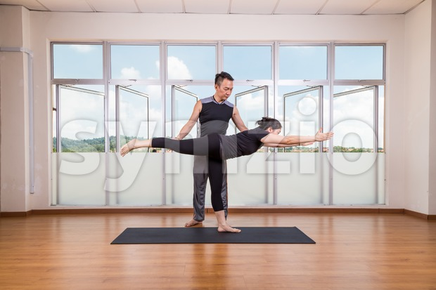 Yoga instructor correcting student performing Warrior 3 or Virabhadrasana 3 Stock Photo