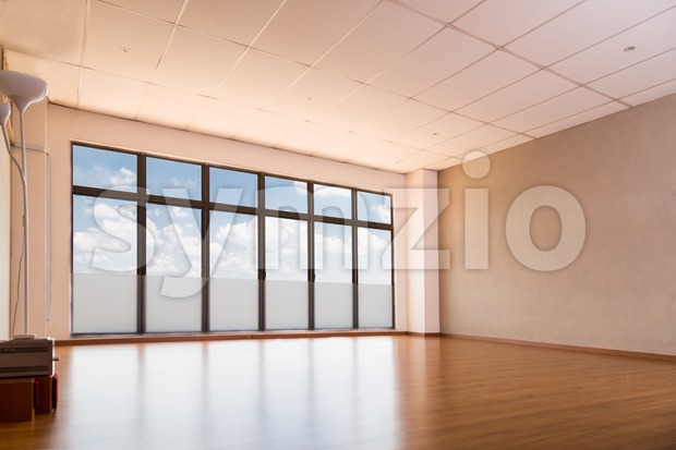 Empty yoga studio with wooden flooring, windows with blue sky and clouds