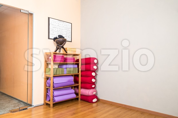 Yoga blocks, pillow, mats, pads, accessories stacked in empty yoga studio with wooden flooring
