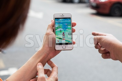 KUALA LUMPUR, MALAYSIA, JULY 16, 2016: An IOS user plays Pokemon Go, a free-to-play augmented reality mobile game developed by Niantic for iOS and Stock Photo