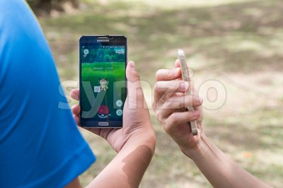 KUALA LUMPUR, MALAYSIA, JULY 24, 2016: Two users play Pokemon Go, a free-to-play augmented reality mobile game developed by Niantic for iOS and Stock Photo