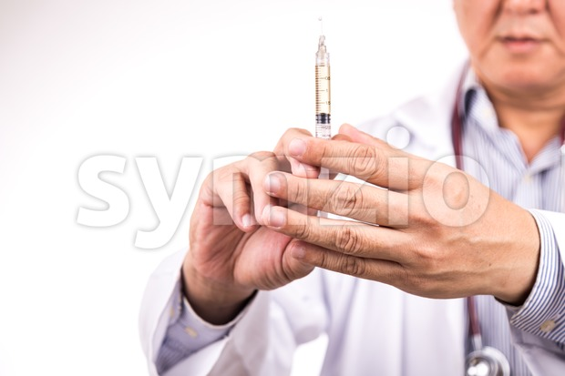 Closeup of medical doctor hand holding syringe for injection Stock Photo