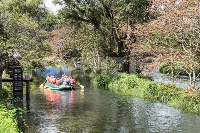 Group of people on raft peddling on serene scenic river Stock Photo