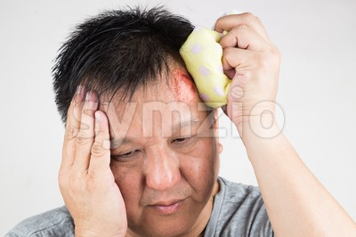 Man treating his injured painful swollen forehead bump with icepack Stock Photo