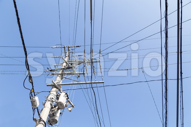 Electricity pole with wires grid with blue sky Stock Photo