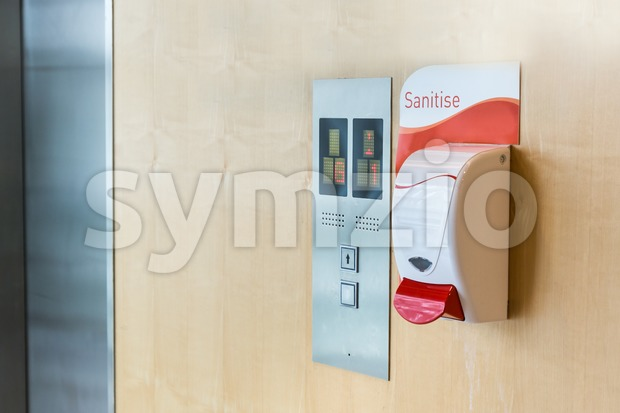 Public hand sanitizer next to elevator Stock Photo