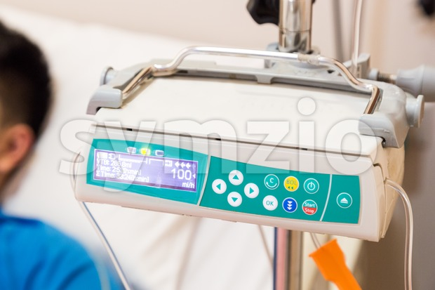 IV infusion pump regulator with patient at background Stock Photo