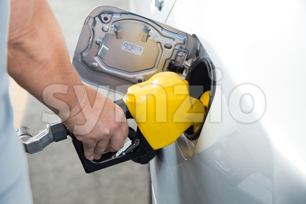 Hand with nozzle fueling unleaded gasoline into car Stock Photo