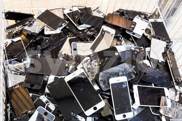 Stack and piles of damaged smart phone body and cracked LCD screen in bin.