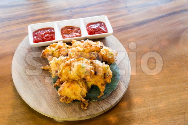 Cucur bawang or onion fritters with dips, popular Malaysia food