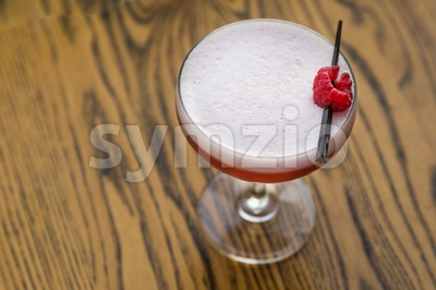 Red cocktail with cherry on table top Stock Photo