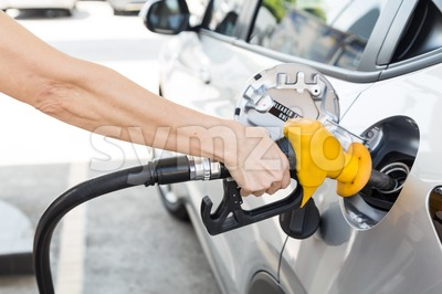Person holding yellow nozzle filling petrol into car Stock Photo