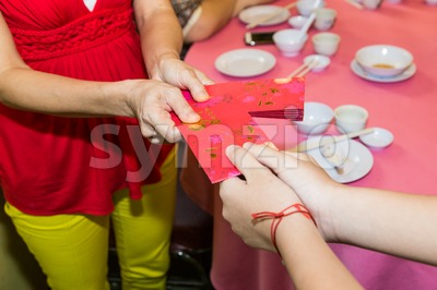 Chinese person giving red packet with Good Luck Chinese word Stock Photo