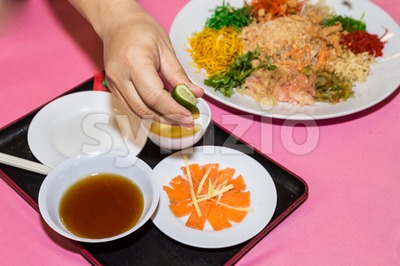 Person preparing Yee Sang or Yusheng Chinese delicacy Stock Photo