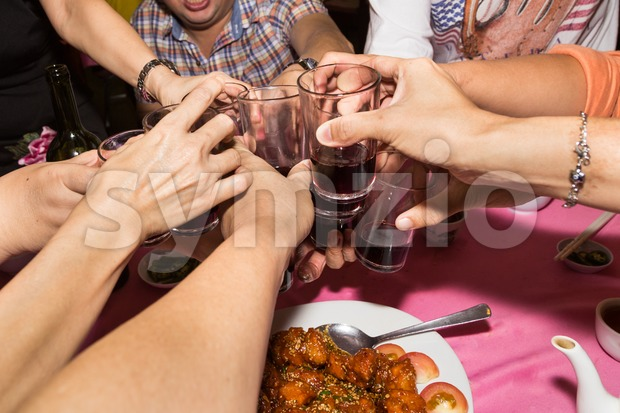 Group of Chinese toasting wine during meal celebration in restaurant