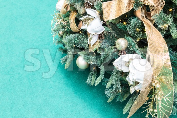 Closeup of Christmas tree with golden ornaments and green background