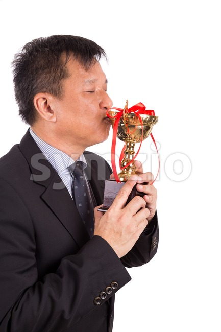 Asian business man in suit kissing golden trophy Stock Photo