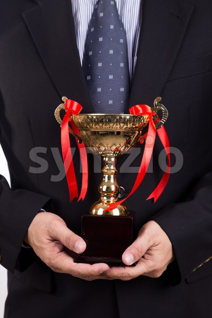 Asian business man in suit holding golden trophy Stock Photo