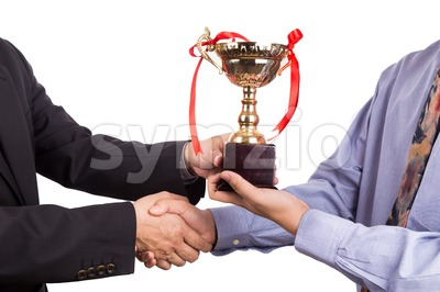 Asian business man shake hand and receive golden trophy Stock Photo