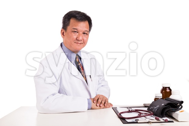 Matured Asian medical practitioner seated behind desk Stock Photo