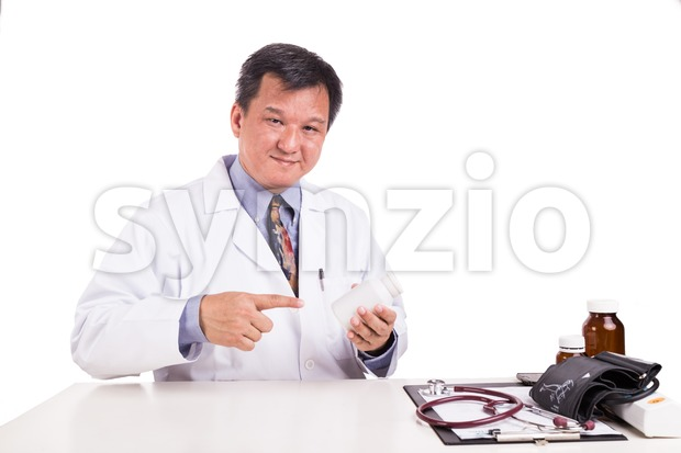 Matured Asian medical practitioner pointing on medicine bottle Stock Photo
