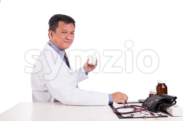 Matured Asian medical practitioner holding medicine seated behind desk Stock Photo